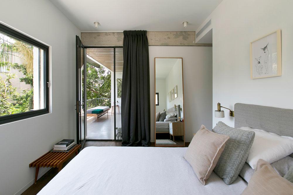 חדר השינה נקי ובהיר, עם יציאה למרפסת המשותפת לסלון. שלושה רישומים מעל המיטה, מראה עצומה שנשענת על הקיר, ומנורת תקרה שעלתה 20 שקל (צילום: שירן כרמל)