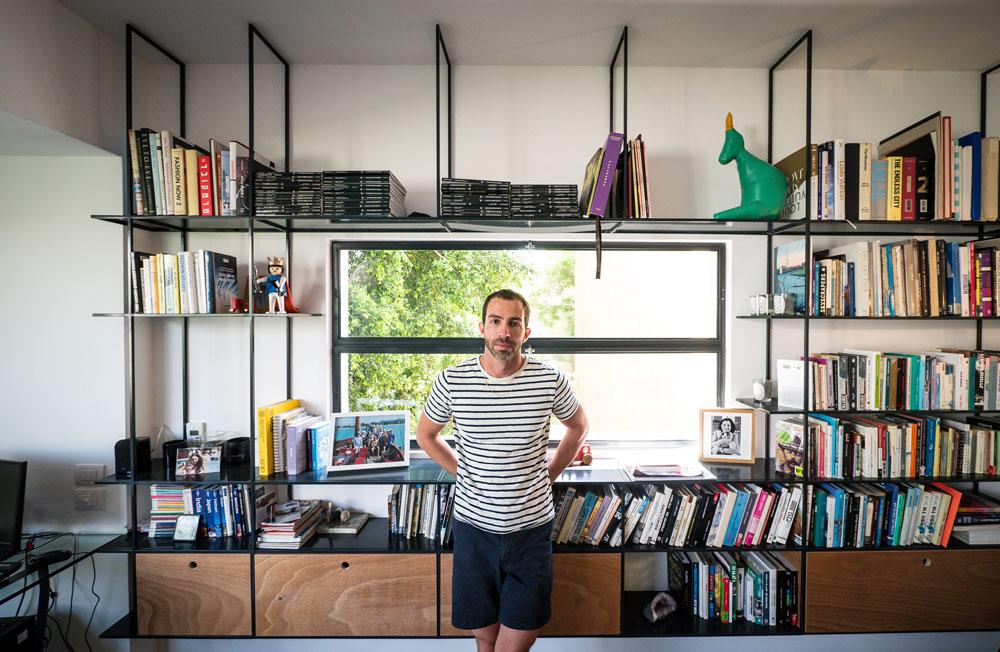"""אורי להבי בדירתו. """"תמיד גרתי בתל אביב, ואני לא מדמיין את עצמי חי בעיר אחרת, אבל הבית הנוכחי הוא לא בהכרח הבית האחרון שלי"""" (צילום: איתי סיקולסקי)"""