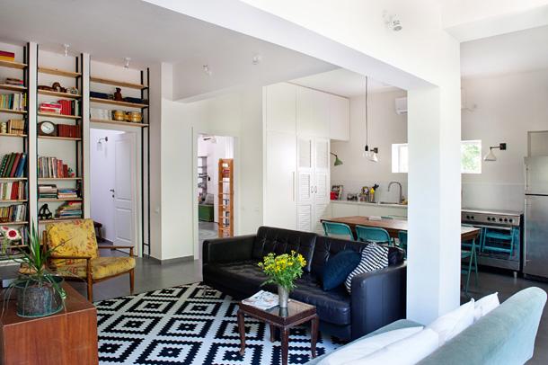 שטיח גיאומטרי בשחור-לבן, כורסת וינטג' וספריית עץ וברזל שחור בדירה שעיצבה דלית לילינטל (צילום: גלית דויטש)