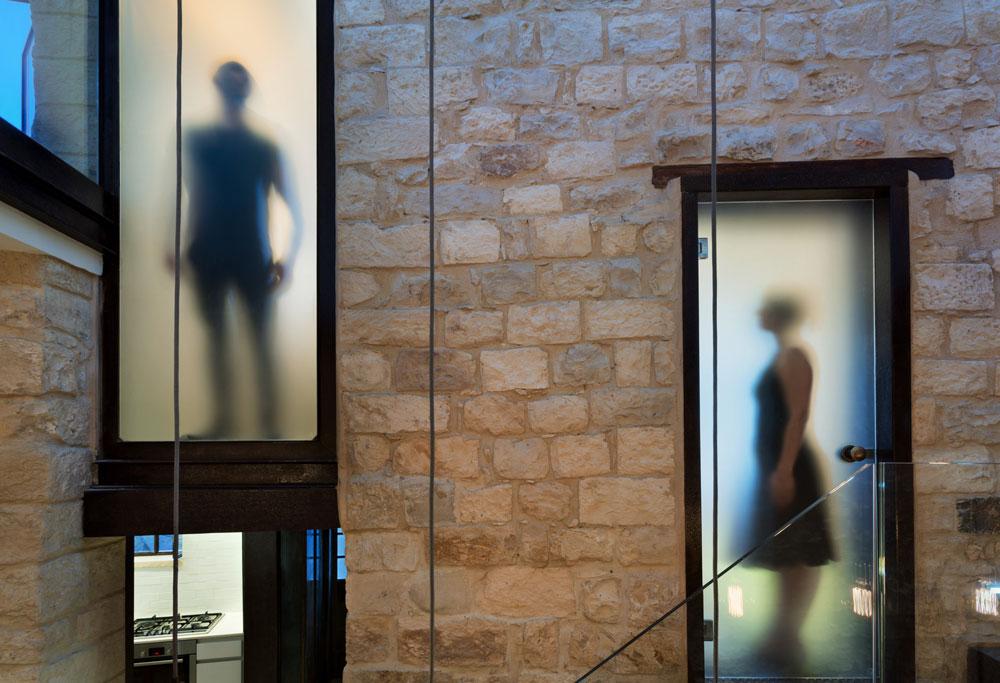משחק בין החלקים השקופים והגלויים, באמצעות דלתות מזכוכית חלבית. כאן נראים מפלסי הביניים, ובפינה השמאלית למטה נראית הכניסה לבית (צילום: אסף פינצ'וק)
