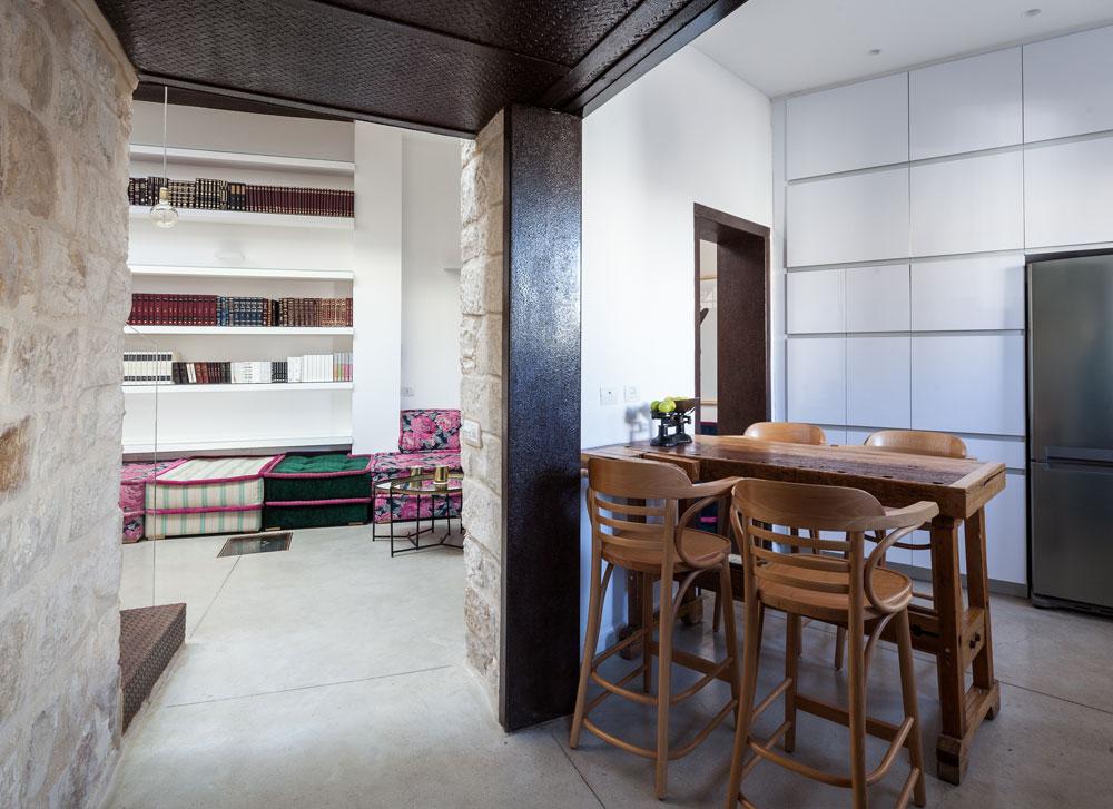 מבט ממבואת הכניסה אל המטבח ואל פינת הישיבה, שמוקמה במה שהייתה חצר פנימית. הספה צבעונית במיוחד, ''שיהיו אנרגיות חיוביות'', מסבירה בעלת הבית (צילום: טל ניסים)