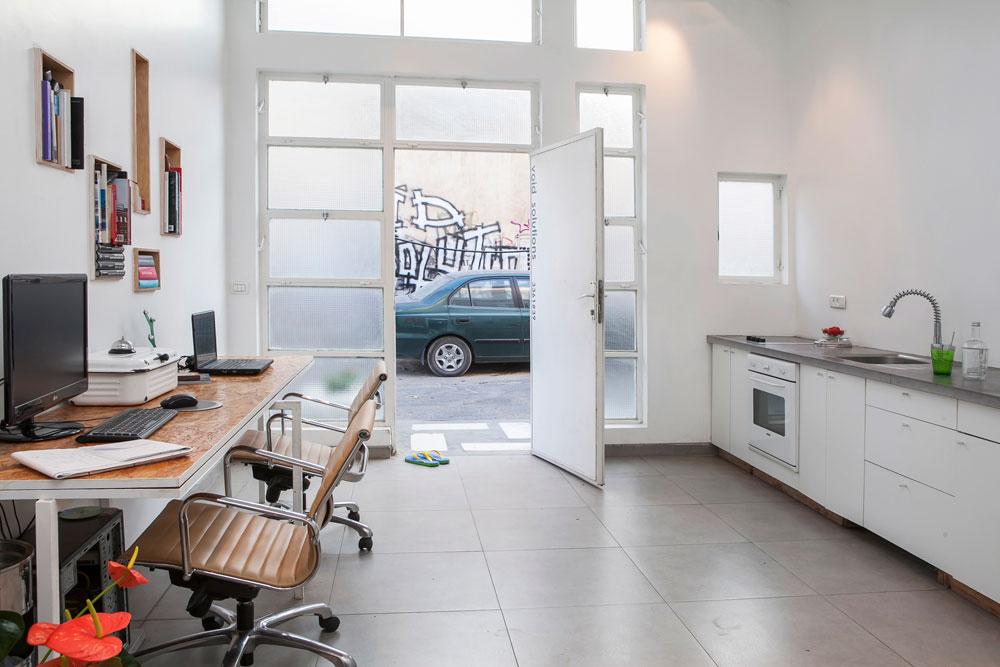 בחלל הכניסה נמצא מצד אחד המטבח הביתי ומצד שני שולחן העבודה הארוך שבנו בעצמם ומתפקד כמשרד האדריכלים העצמאי והקטן שפתחו  (צילום: שירן כרמל)