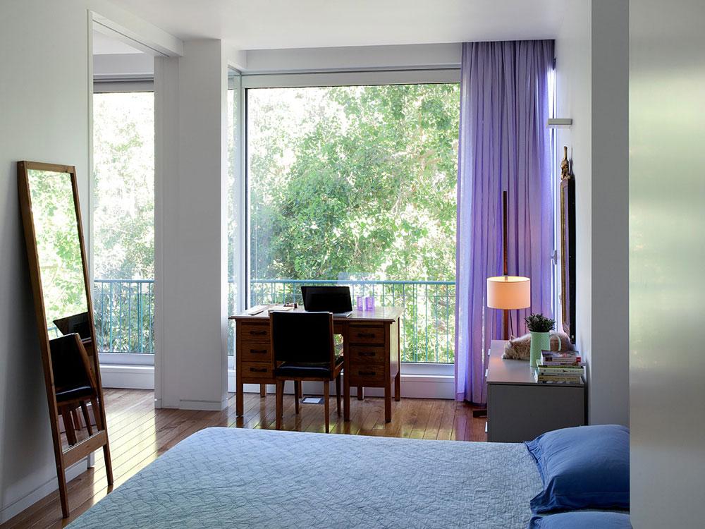 חדר השינה של ההורים, שבו שתי דלתות: אחת נפתחת למסדרון, מול חדר הרחצה, והשנייה היא דלת הזזה גדולה בקיר המשותף עם הסלון. כאשר היא פתוחה נשמרת תחושת המרחב שאליה התרגלו ההורים בשנים שבהן ישנו בסלון. וילון סגול שקוף נתלה על החלון הגדול, בחירה של בעלת הבית, שגילתה, לדברי עמיר, רגישות יוצאת דופן לצבע: ''הצבעים שבחרה מאפשרים לצבעוניות נוספת 'לחיות' סביבם'' (צילום: אלעד שריג)