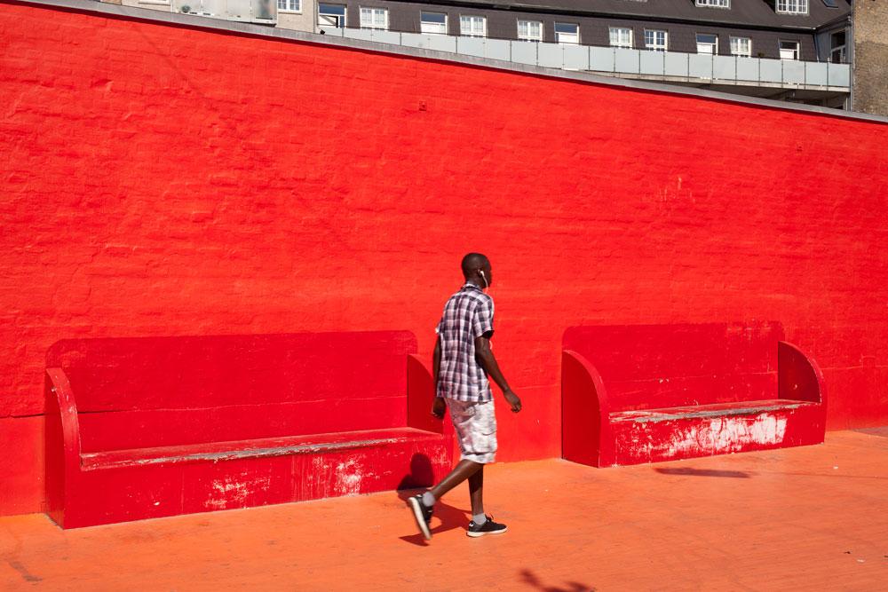 מהגר אפריקאי פוסע באזור הרחבה האדומה. זהו משטח גמיש שמאפשר לערוך עליו אירועי תרבות וספורט. הטריבונות ניידות והן מגיעות מהמתנ''ס הקרוב (צילום: Torben Eskerod)