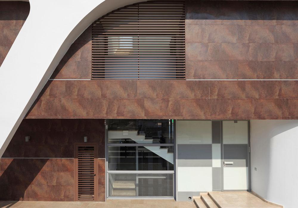 דלת הכניסה. המעטפת החיצונית בולטת בלובנה על רק החיפוי החום של הבית (צילום: שי אפשטיין)