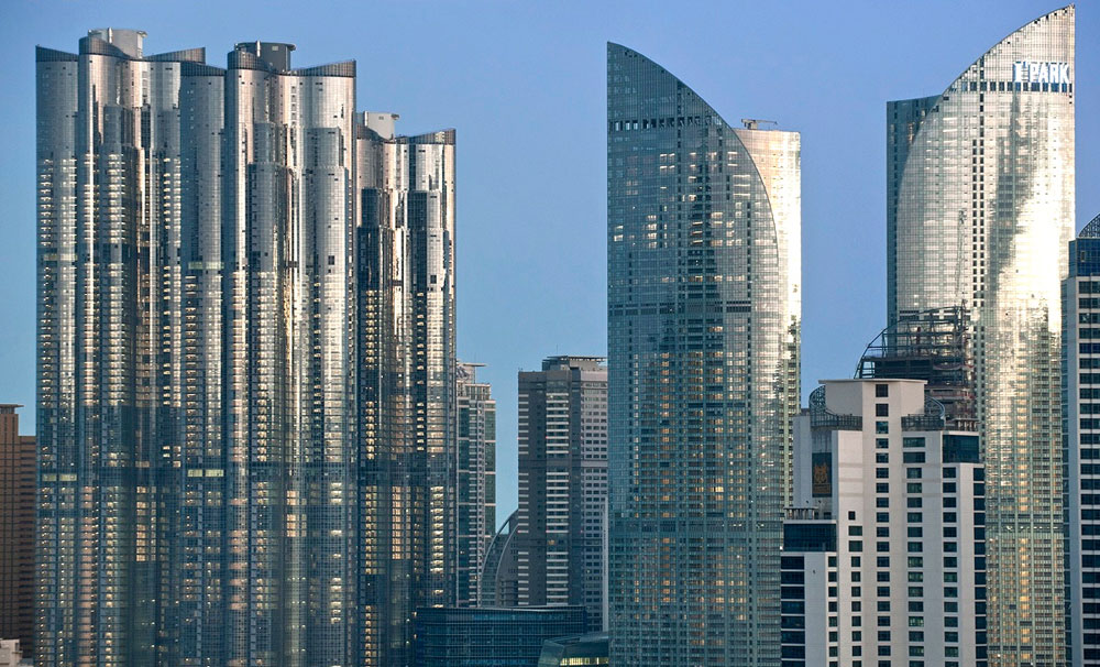 שכונת המגדלים הנוצצת עם השם הממותג  We've the Zenith בבוסאן, העיר השנייה בגודלה במדינה. שלושה צילינדרים מאונכים, שאחד מהם מתנשא לגובה 80 קומות והוא השמיני בגובהו בעולם (צילום: cc,Pointcode)