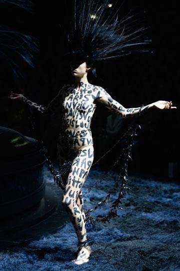 דגמים תיאטרליים בצבע שחור ונוצות על הראש. התצוגה של לואי ויטון (צילום: gettyimages)