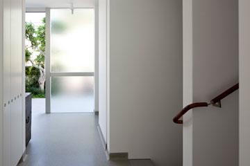 דלת הכניסה הוטמעה בחלון גדול שמאיר את המבואה (צילום: עמית גרון)