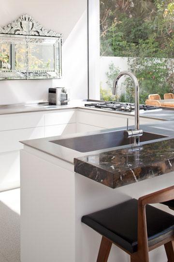 המטבח. ארונות לבנים, משטח עבודה דק מנירוסטה ודלפק משיש בגוני חום ושחור  (צילום: עמית גרון)