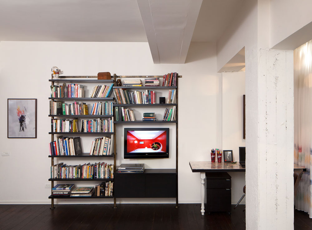 מסך הטלוויזיה שולב בתוך ספרייה גדולה כדי שלא יתבלט. היא נבנתה מעמודים מקוריים שנמצאו בשוק הפשפשים ומדפים שהוזמנו אצל נגר (צילום: טל ניסים)