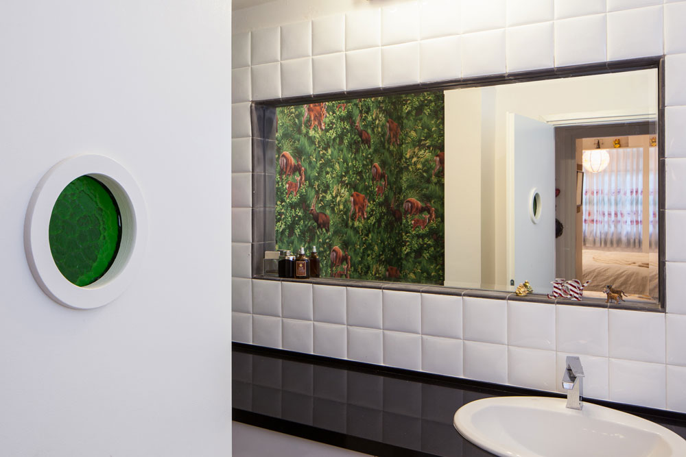 חדר הרחצה עוצב גם הוא בהשראת הסבנטיז. טפט נועז הודבק על הקיר היבש בחדר, כדי לשבור את הניקיון הסניטרי של השחור-לבן (צילום: טל ניסים)