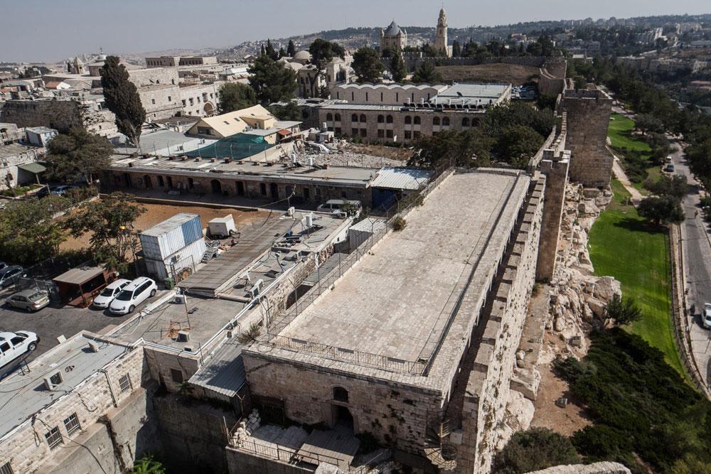בחזית: המבנה המלבני שצמוד לחומה העותמאנית, שמתחתיו נעשתה החפירה. הגג הוא חלק מטיילת החומות, והמבנה נמצא בקצה מתחם תחנת הקישלה של משטרת ישראל (צילום: טל ניסים)