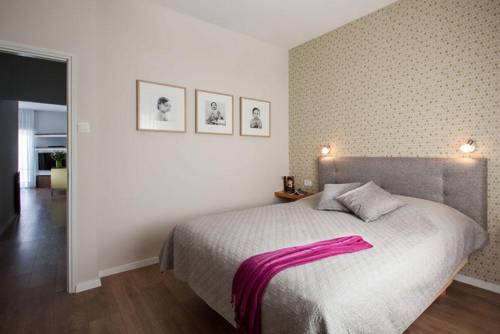 חדר ההורים, ''אחרי''. המיטה רופדה והותאם לה טפט, מדפים שנבנו בצורה א-סימטרית משמשים כשידות צד, ועל הקיר תמונות של הבת (צילום: טל ניסים)