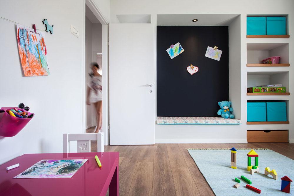 חדר המשחקים. ארון קיר גדול פורק ובמקומו נבנו שלוש נישות גבס, שבגדולה שבהן ספסל מרופד על רקע קיר שנצבע בצבע מגנטי, ואליו אפשר להצמיד ציורים (צילום: טל ניסים)