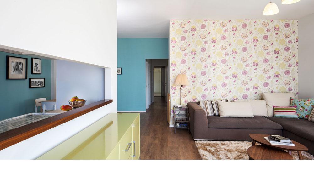 המעצבת סיון קונוולינה התאימה את בדי הריפוד לגוני הקיר והטפט. הסלון עוצב בצבעים עדינים של ורוד וחרדל, המבואה נצבעה טורקיז, וחלון צר מאפשר קשר עין עם המטבח (צילום: טל ניסים)