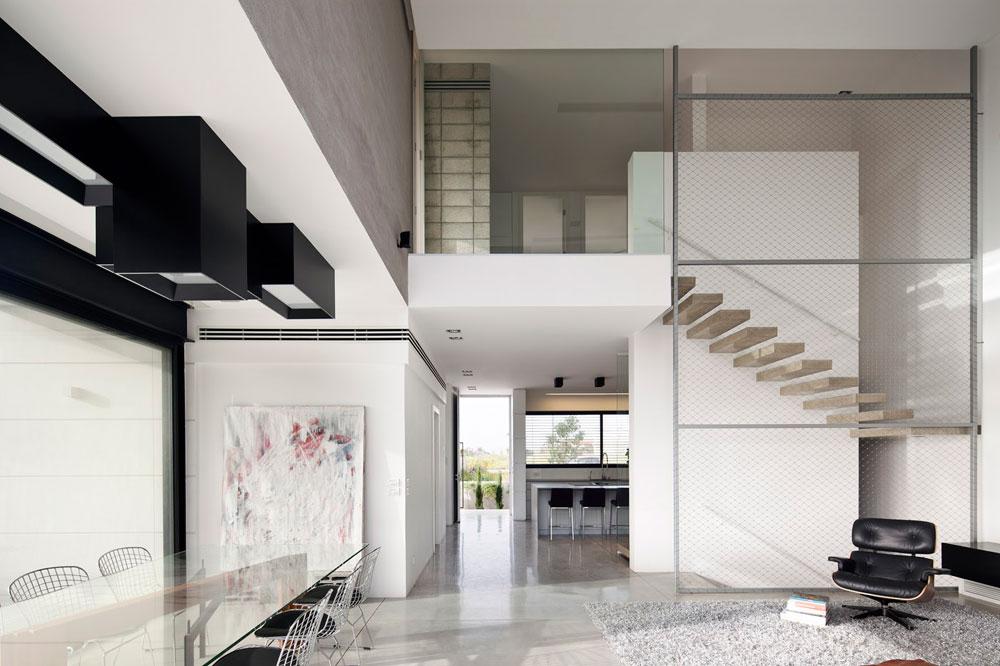 קומת הכניסה תוכננה כמרחב פתוח ונטול קירות כמעט, למעט קיר מלבני שניצב במרכזה ועליו תלויות המדרגות המובילות לקומה העליונה. גובה הסלון כפול, כגובה גרם המדרגות. במקום מעקה מגונן עליהן מסך שנמתח מהרצפה עד לתקרה, ועשוי רשת נירוסטה בדוגמת מעוינים, כמו בגדרות הפשוטות ביותר (צילום: עמית גרון)