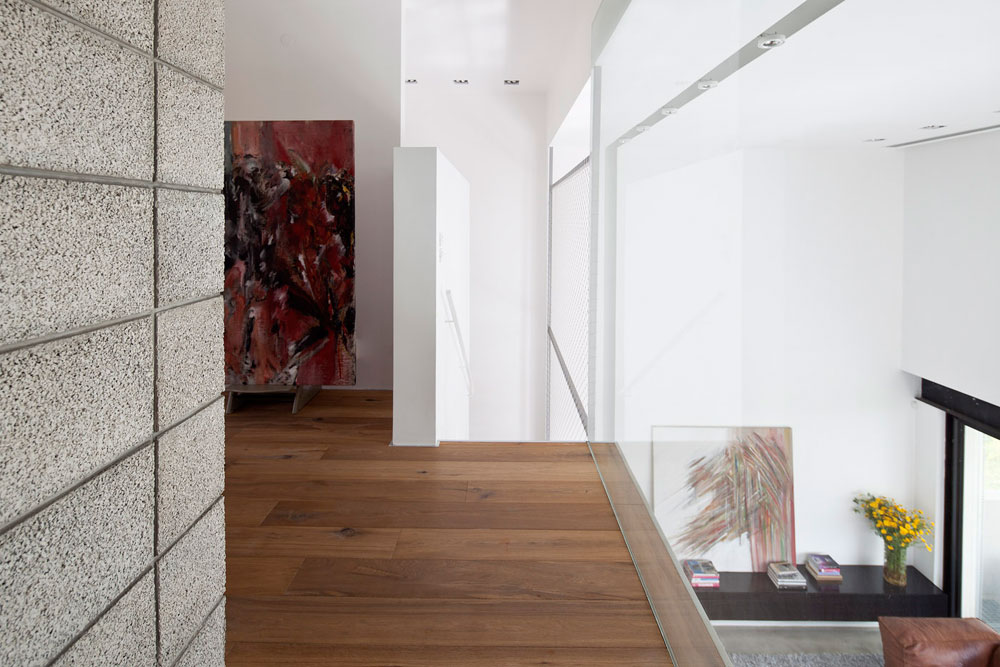 המבואה לחדרי השינה שלמעלה נהנית מהאור הטבעי החודר לסלון בזכות מעקה הזכוכית. הרצפה מחופה עץ, ושני האלמנטים הבולטים הם קיר לבנים חשופות וציור נוסף של ספרן גורפונג (צילום: עמית גרון)