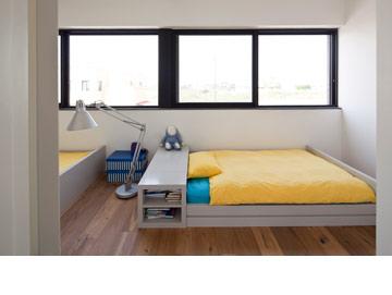 חדר הילדים. מיטות רחבות מתחת לחלון, עם מקום לאחסון בראש המיטה (צילום: עמית גרון)