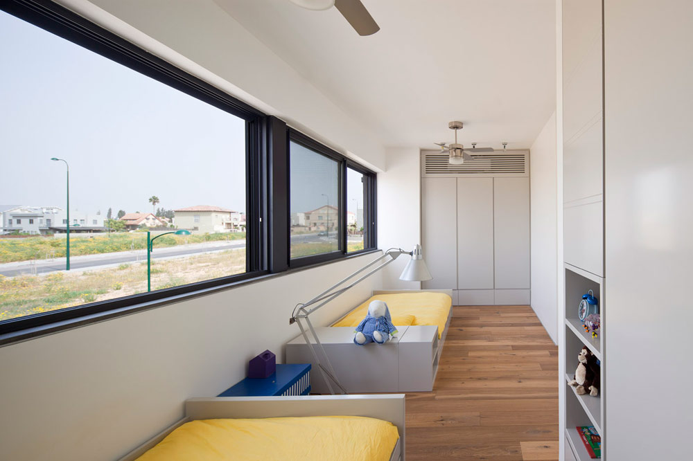 שניים מחדרי הילדים אוחדו לחלל ארוך. מתחת לחלון-סרט הוצבו מיטות רחבות, צבועות באפור. ראש המיטה משמש גם כספרייה ומקום אחסון (צילום: עמית גרון)