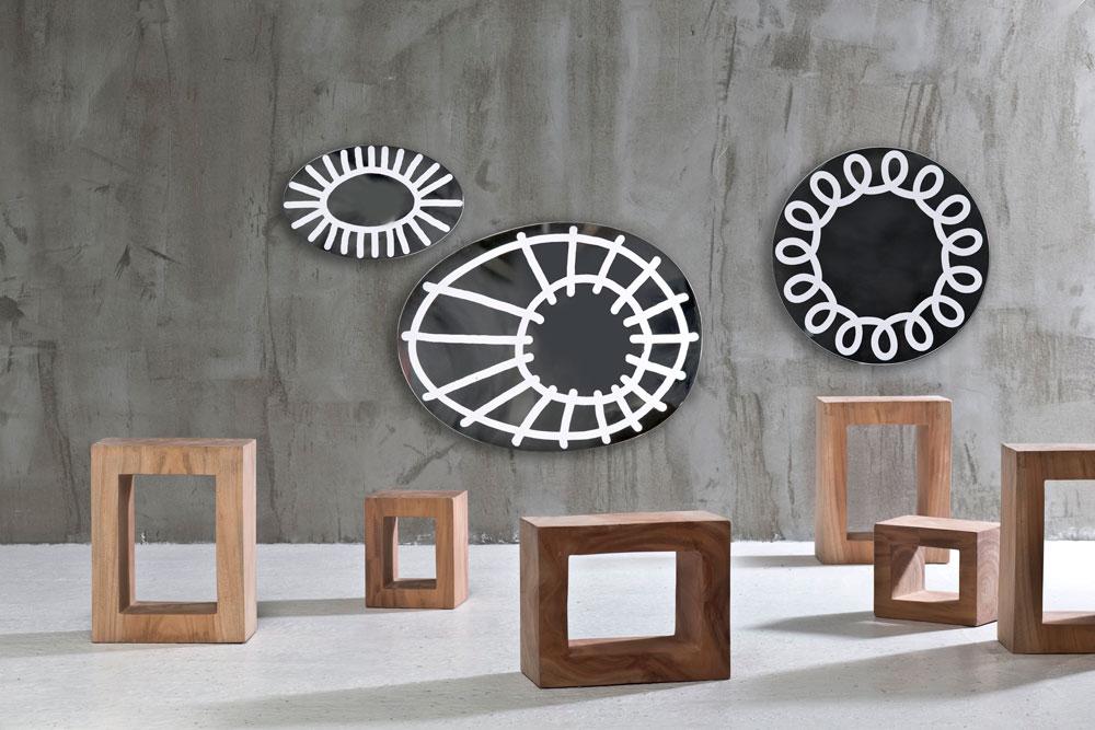 מתוך קולקציית ''בריק'' של פאולה נבונה.  מערכות ישיבה, פריטים משלימים מעץ גולמי ואוסף מראות שעליהן הדפסים גרפיים בלבן (באדיבות טולמנס)