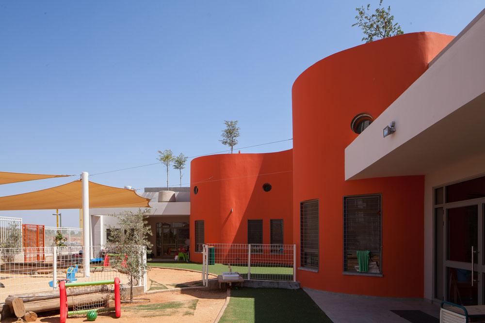משטחי צבע בוהקים בגן הילדים בגני תקווה. המגרש המשולש הכתיב עיצוב אמורפי של מעטפת המבנה (צילום: טל ניסים)