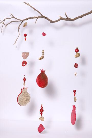 זהב אדום. מובייל רימונים תלוי על ענף עץ (צילום: ענבל עופר)