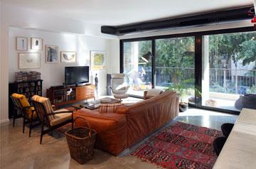 בסלון יש ספת עור, שולחן קפה, שתי כורסאות ששופצו, כורסה והדום לבנים בעיצוב ריי וצ'רלס אימס. מול הספה: שידה וטלוויזיה (צילום: עוזי פורת)