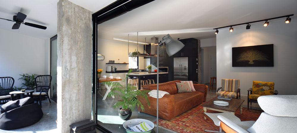 מבט מהמרפסת החזיתית, שנסגרה בידי  בעלי הבית הקודמים ונפתחה מחדש. הסלון רוהט בעיקר ברהיטים ישנים בצבעים חמים, והמטבח - כמו אלמנטים אחרים בדירה - עוצב בשחור ולבן (צילום: עוזי פורת)