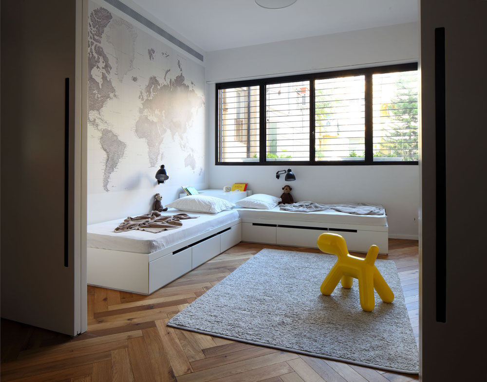 בין 3 החדרים מפרידות דלתות הזזה לבנות עם מגרעות שחורות. על הקיר מעל המיטה הודבק טפט של מפת העולם, באפור ולבן. הרצפה כוסתה בפרקט עץ אלון בצורת אדרת דג, כמו באגף ההורים (צילום: עוזי פורת)
