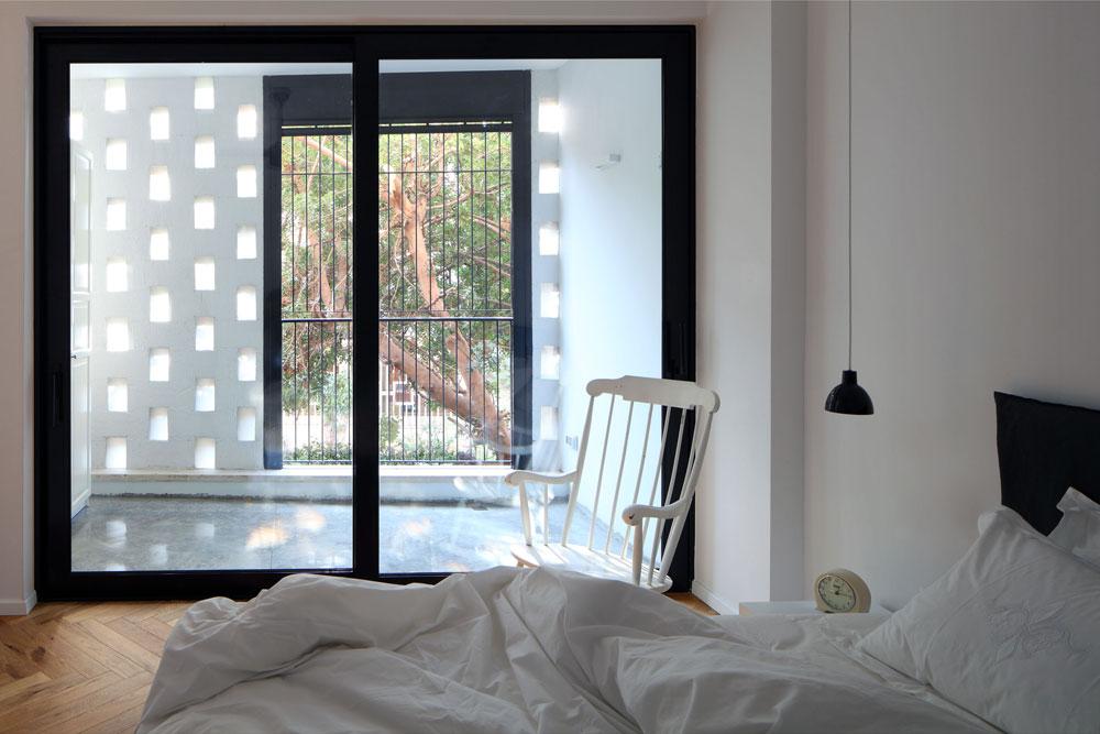 חדר ההורים נזירי כמעט, עם מעט רהיטים וסקלת צבעים של שחור-לבן ועץ. חלון זכוכית גדול מפריד בין החדר למרפסת חצי סגורה, שצופה לרחוב קטן שיוצא מהשדרה. האור מסונן באמצעות קיר לבנים במראה שתי וערב, שאופייני לבנייה התל אביבית של שנות ה-50 ולוקח השראה מהמשרבייה האסלאמית  (צילום: עוזי פורת)
