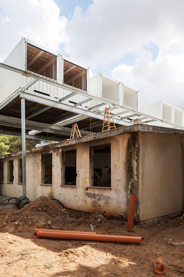 בית הספר הישן הושאר, המכולות מרחפות מעליו (צילום: אביעד בר נס)