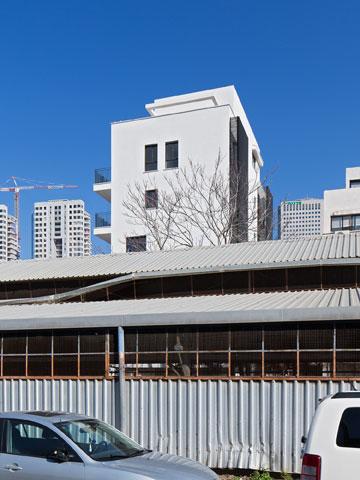 מוסכים הם חלק בלתי נפרד מהמציאות. מאחור: הבניין החדש (צילום: אלעד שריג)