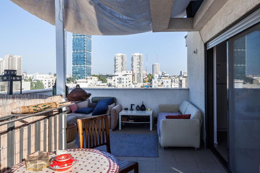 בדירת-הגג הדו-מפלסית גרה משפחה, שהוציאה את הסלון למרפסת. גם כאן, המחיר הנמוך היה סיבה מובילה למעבר ממרכז העיר (צילום: טל ניסים)
