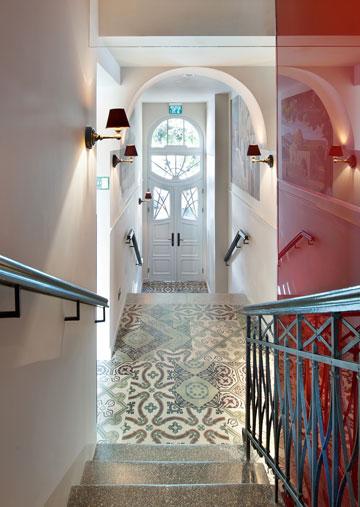 מהכניסה לבית שפרן עולים, במעלית בצבע עגבנייה, היישר לסוויטות שעל הגג. האריחים המצוירים שומרו, פרטי העיצוב בוצעו בקפדנות (צילום: עמית גושר)