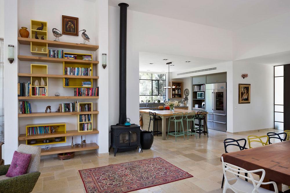 קמין וספרייה שהוזמנה במיוחד מפרידים בין הסלון למטבח. רוב הרהיטים הובאו מביתם הקודם של בני הזוג (צילום: שי אפשטיין)