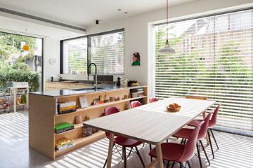 שולחן אוכל מעץ של החברה הדנית HAY, ולצידו מדפים צרים עם פריטים דקורטיביים (צילום: טל ניסים )