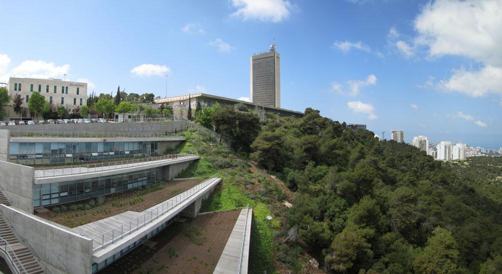 מבט לבית הסטודנט באוניברסיטת חיפה מכיוון צפון-מזרח. המרחב הציבורי פתוח, מגונן ופונה אל נוף מרהיב, אבל הפעילות החברתית העיקרית היא בקפטריות (באדיבות דוברות אוניברסיטת חיפה)