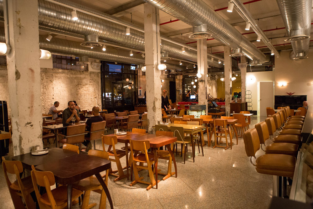 ''מגזינו'' בדרום תל אביב. ממוקם במבנה תעשייתי לשעבר, בפינת רחובות סואנת במיוחד, לא רחוק מחפירות הרכבת הקלה. העיצוב מחוספס בהתאם, ופונה לקהל צעיר ולילי (צילום: אורית פניני)