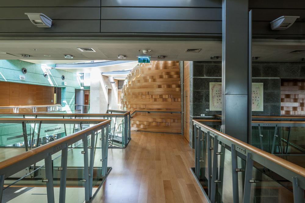 גשרים בקומה השנייה מובילים לחדרי פעילויות וחוגים. הקומה הפתוחה עם המבט למבואה מזכירה עיצוב קניון (צילום: טל ניסים)