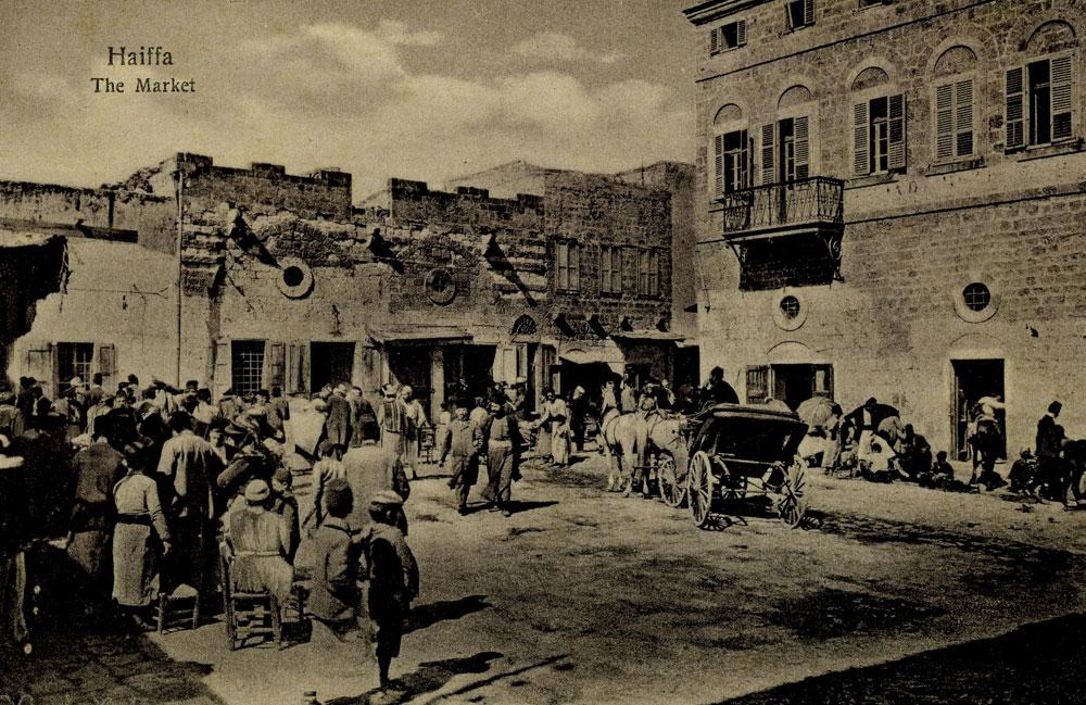השוק בעיר התחתית בחיפה, 1910. התערוכה מסתיימת ב-1930, עם כניסת הבטון והסגנון הבינלאומי ושקיעת הבנייה המסורתית (אוסף אלי רומן)