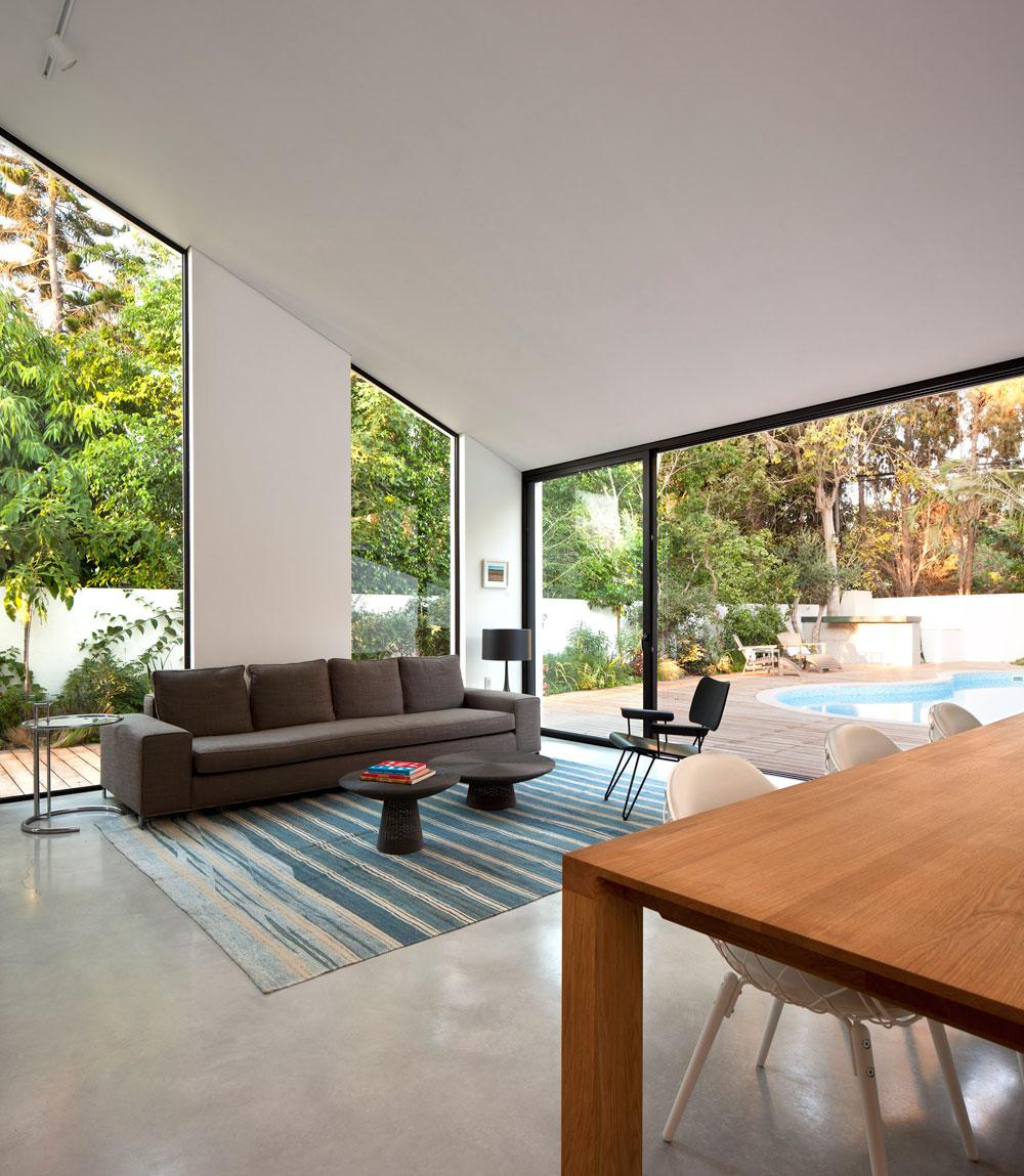 הרצפה חופתה בבטון טבעי מעונן, לא אחיד. החלונות ''מלווים'' את תוואי הגג המשופע ונבחר להם אלומיניום שחור (צילום: עמית גרון)