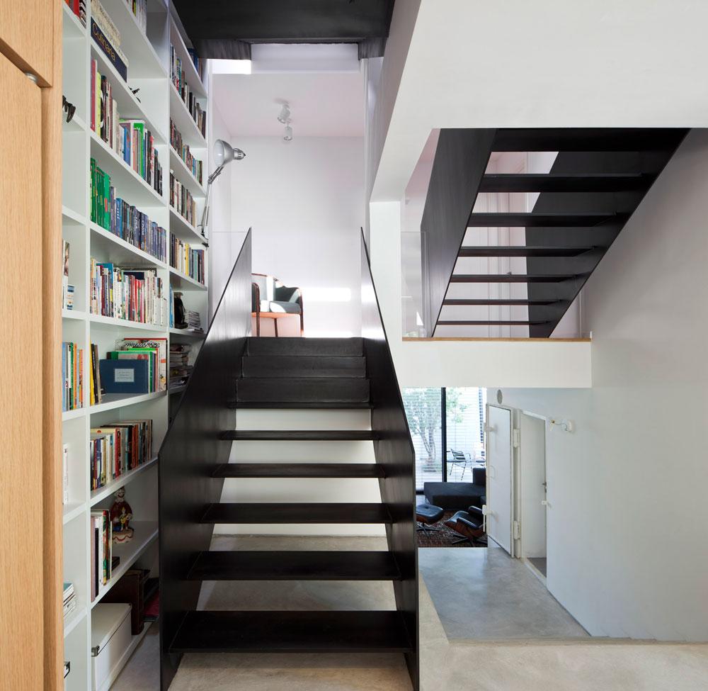 המדרגות עשויות ברזל שחור, ועל הקיר שלצדן נבנתה ספריית ענק, שמלווה את המדרגות לגובה הבית. בזכותן אין מדפים גבוהים מדי (צילום: עמית גרון)