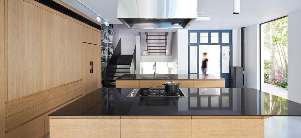 על הקיר המשותף עם בית השכנים נבנו ארונות גדולים במראה טבעי, שמסתירים את המקרר ומכשירי החשמל השונים (צילום: עמית גרון)