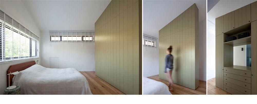 חדר השינה. ארון שגגו משופע (בהתאם לתקרה) חוצץ בין המיטה לחדר הרחצה, ומצדו השני (בתמונה מימין) נבנו בו מדפים ומגירות (צילום: עמית גרון)
