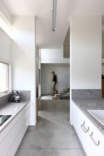 ארונות המטבח מחופים משטח מחומר ממחוזר, הרצפה עשויה בטון במסה משמעותית, שאוגרת אנרגיה בימי החורף (צילום: עוזי פורת)