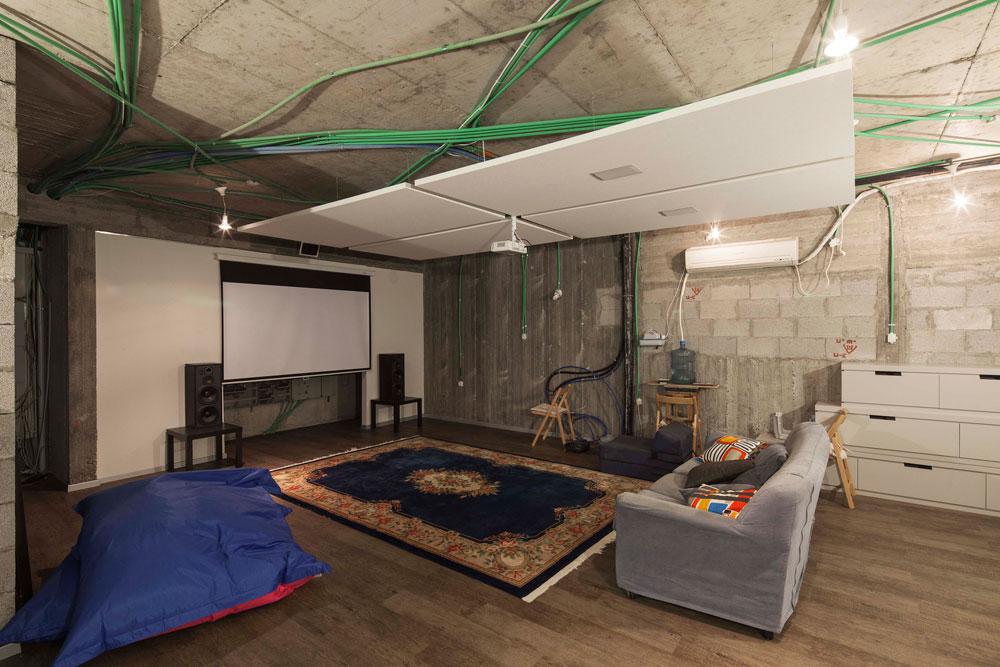 המרתף הוא מעין קולנוע ביתי, שבו הושארו מערכות החיווט וקירות הבטון והבלוקים גלויים, בכוונה תחילה. המרתף אינו מחליף את הממ''ד, שנמצא בקומת הכניסה ומתפקד כמחסן (צילום: אביעד בר נס)