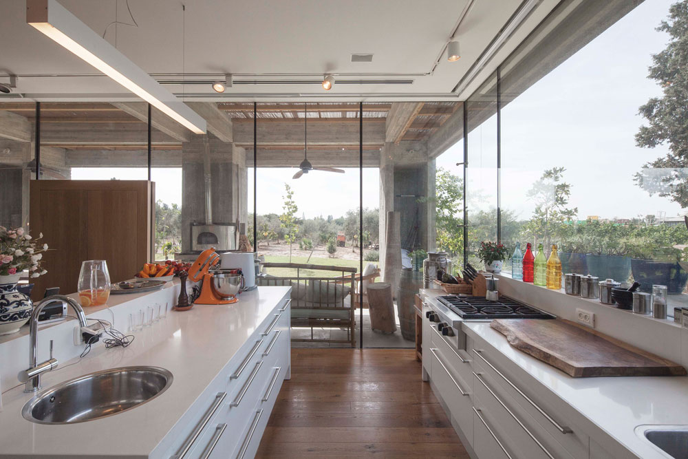 בשונה מיתר הבית, המטבח תוכנן בסגנון מודרני ולבן. אב המשפחה אוהב לבשל, ופונקציונליות במטבח היתה לו חשובה. רהיטי הגן הנראים מבפנים יובאו מבאלי שבאינדונזיה (צילום: אביעד בר נס)