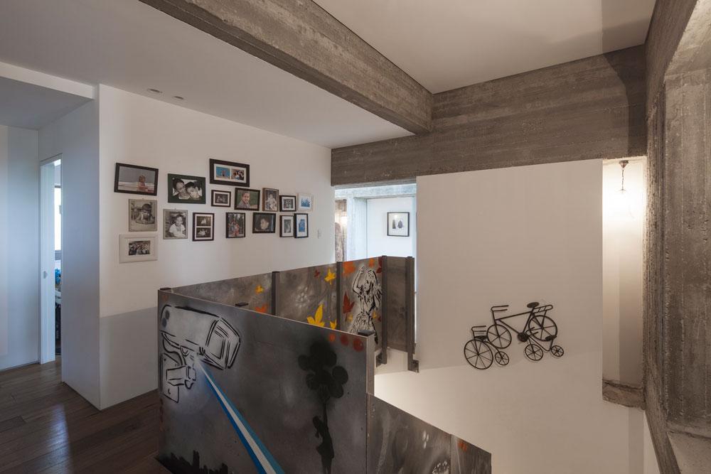 גרם המדרגות המוביל מאגף הילדים למרתף מוקף מעקה פלדה שעוטר בגרפיטי. חדרי השינה לבנים כולם, ללא בטון חשוף (צילום: אביעד בר נס)