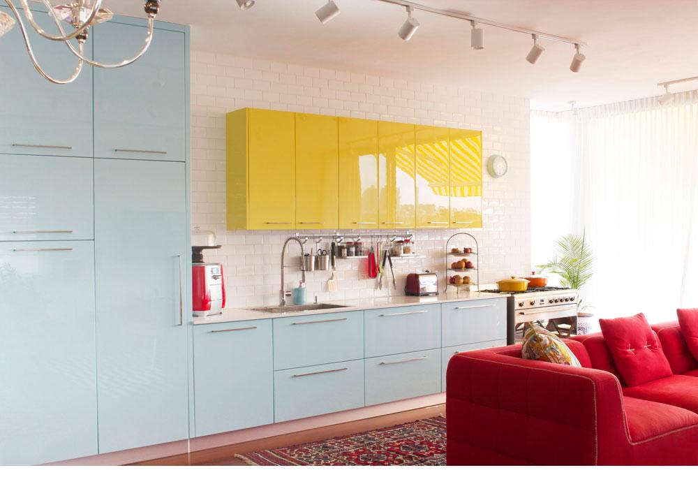 המטבח הוזז ממיקומו המקורי בתוכנית הדירה אל הקיר הארוך שבגב ספת הסלון. צבעיו השמחים והבוהקים משתלבים היטב בחלל (צילום: אפרת לוזנוב)