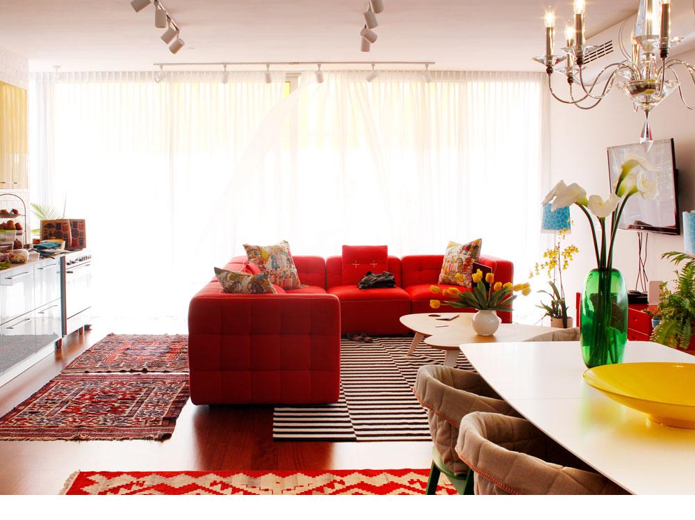 במרכז הסלון ספת ר' מודולרית בצבע אדום-ורוד, עם תיפורים לבנים בולטים. על הרצפה שטיחים בדוגמה גיאומטרית ווילונות לבנים מסננים את האור שחודר דרך קיר הזכוכית שנפתח למרפסת (צילום: אפרת לוזנוב)